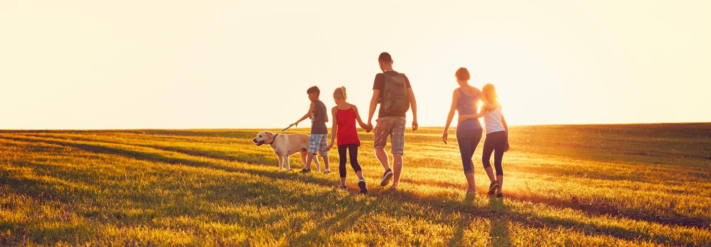 a dad and mom with three children and a yellow lab walking through short grass