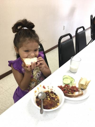 a young girl eating lunch
