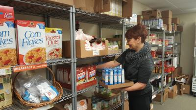woman stocking shelves in a food pantry