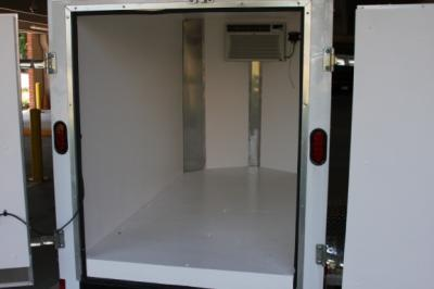 An empty inside of a medium-size trailer. A cooling unit can be seen at the back of the storage place.