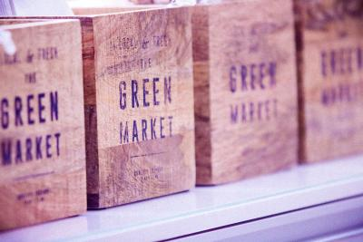 A row of CSA subscription boxes with the words Green Market printed on them.