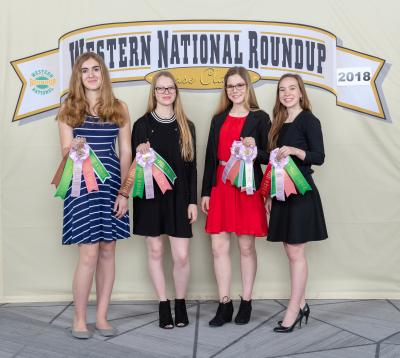 four women holding their award ribbons