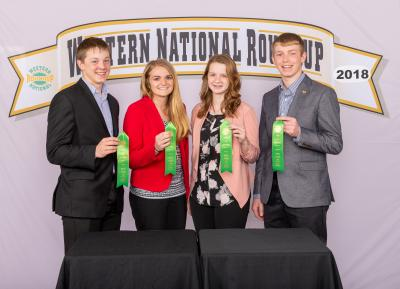 four individuals holding their award ribbons