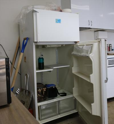 an white refrigerator with an open door. lunch pails and a bottled beverage are inside. a sink and kitchen area are next to it.