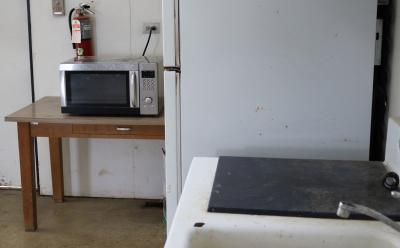 silver and black microwave sitting on a brown table next to a white fridge and a sink.