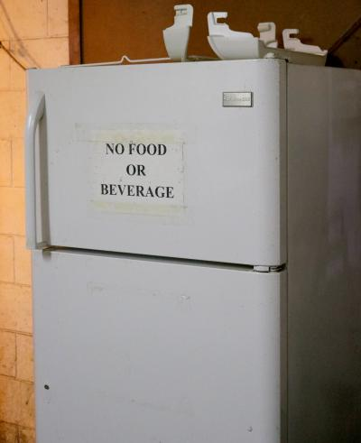 "refigerator with ""No Food or Beverage"" sign taped on the outside."