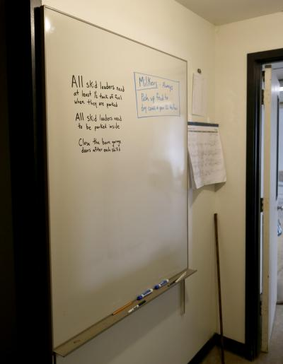 white board mounted on wall with instructions written on it in black and blue marker