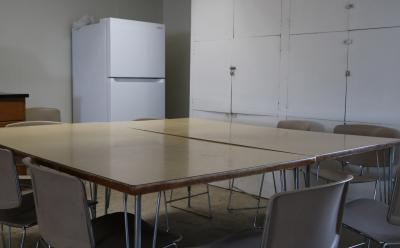 large table with several chairs around it. a refrigerator is in the background.