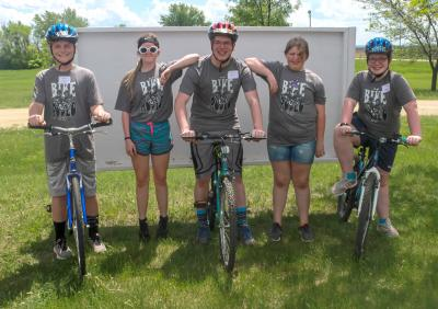 a group of five 4-H youth. two males and one female are on bicycles. two female youth are standing in the background.