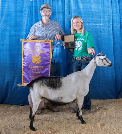 father and daughter holding numerous 4-H awards with their dairy goat