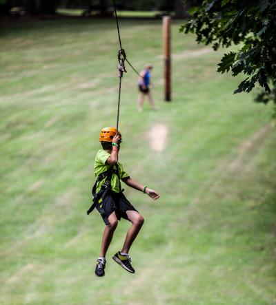 a young male swinging down a zip line
