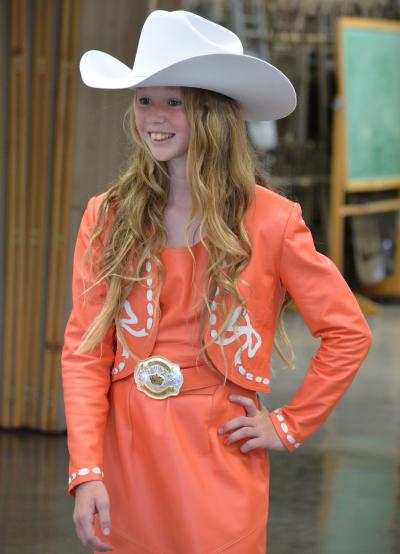 female 4-H youth wearing an orange western-style outfit with a white cowboy hat
