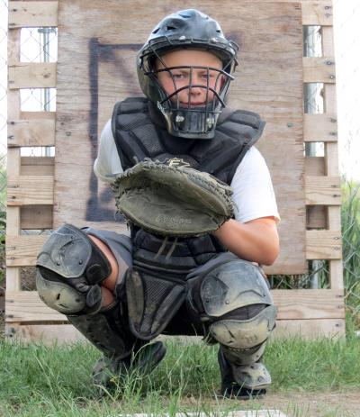 male youth dressed in baseball catcher's equipment