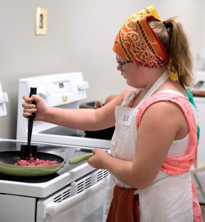 female youth cooking ground beef in a frying pan