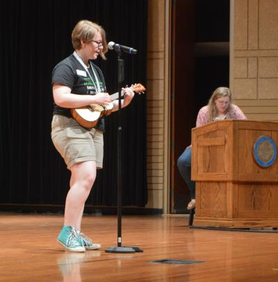 female 4-H youth performing on stage with a ukulele