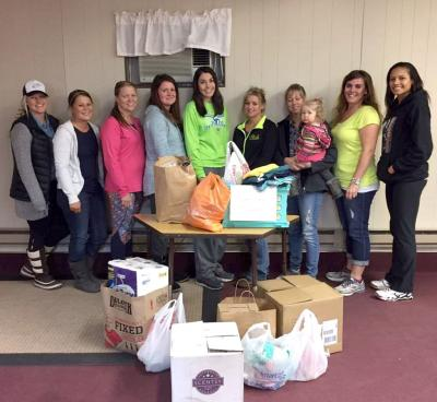group of young women standing by a table of donated items
