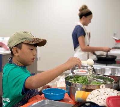 male 4-H youth preparing a salad in a silver mixing bowl
