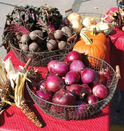 Indian corn, onions, pumpkins, and beets displayed on a table at a farmers market.