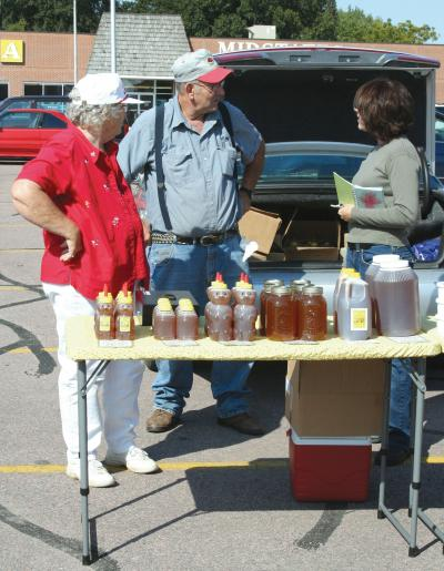An older husband and wife talking with a female vendor near a table displaying honey products at a farmers market.