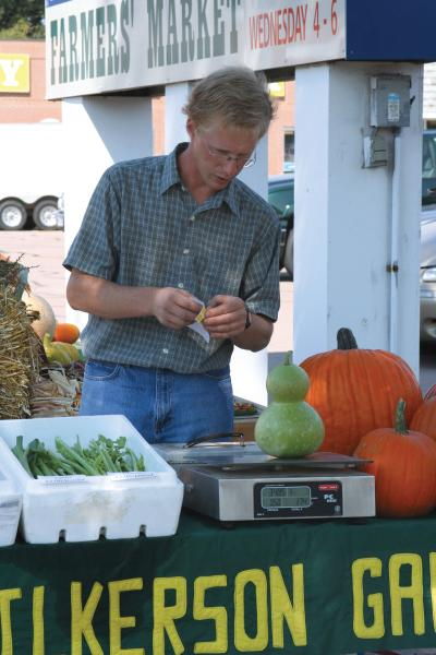 Male merchant weighing a green gourd on a digital scale at a farmers market.