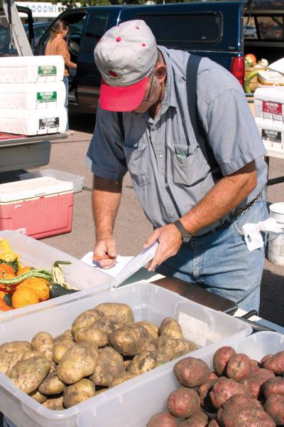 And older male vendor logging sales in a ledger at a farmers market stall.