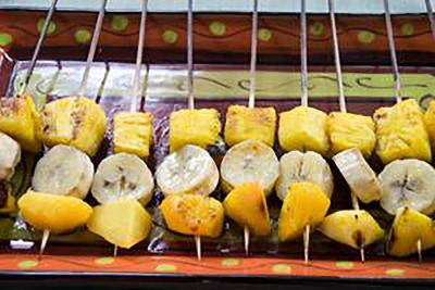 A row of fruit kabobs with pineapple chunks, banana pieces, and peach chunks ready for grilling.