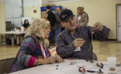 A male conference attendee in a black cap constructing a homemade dream catcher. A woman sitting next to him is closely watching.