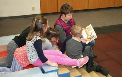 SDSU Extension Early Childhood Field Specialist Audrey Rider reading a book to a group of four children.