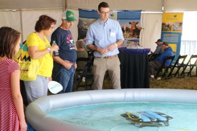 John McMaine, Assistant Professor & SDSU Extension Water Management Engineer, demonstrating an underwater drone in a large pool to a young woman and an older couple.