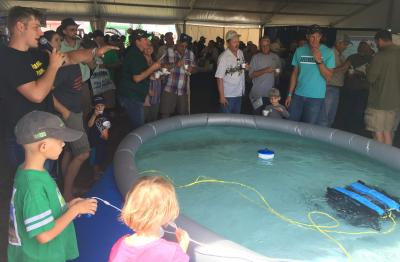 A young boy operating an underwater drone in large pool in front of a crowd of onlookers.