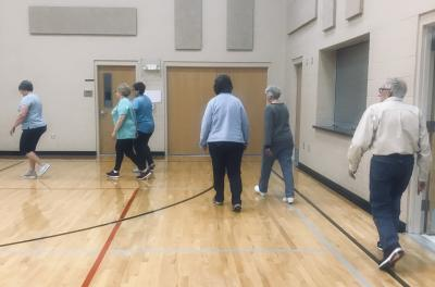five women and one man walking in a gymnasium