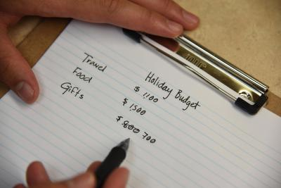 Hands writing out a holiday budget on a notepad.