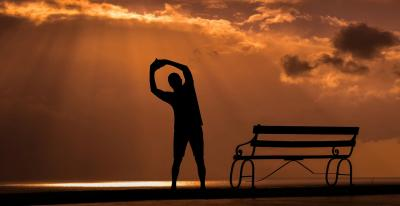 person stretching in front of the rising sun near a bench on the beach