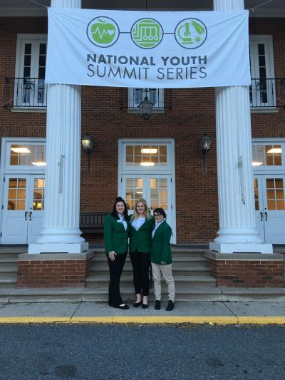 Three women in green jackets standing in front of a building