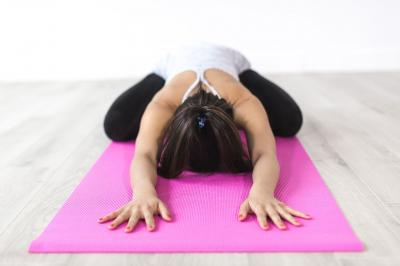 A young woman in workout clothes stretching on a pink yoga mat.