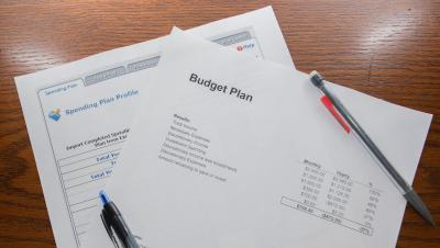 A family budget plan sitting on a desk with a pen and pencil.