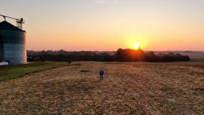 A farmer watching the sun rise in a bare, unplanted field.