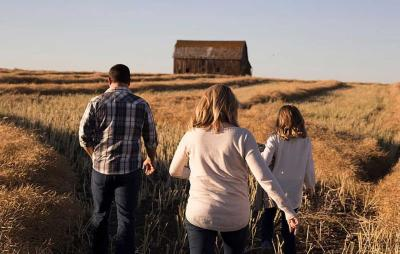 A father, mother and daughter walking in a field in the countryside.