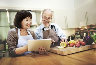 An older couple standing in the kitchen looking at a tablet while cutting a lemon on a wood cutting board