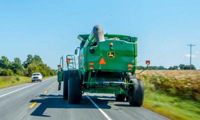 A green combine driving down a paved road.