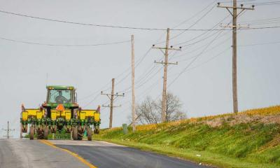 Green tractor driving down a road with low-hanging powerlines across it.