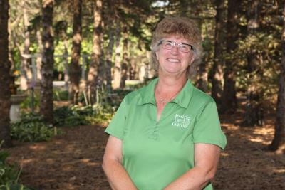 a woman in a green polo standing in front of some trees