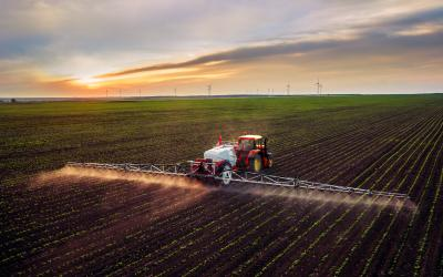 large multi-row sprayer adding chemicals to a field