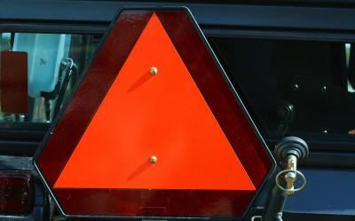 orange reflective safety triangle on a piece of farm equipment
