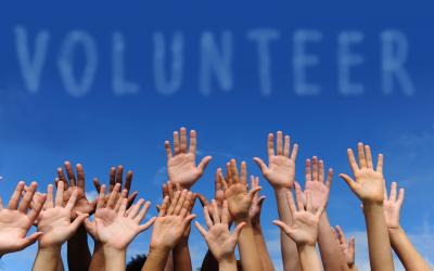 many hands raised in the air with sky background and the word volunteer