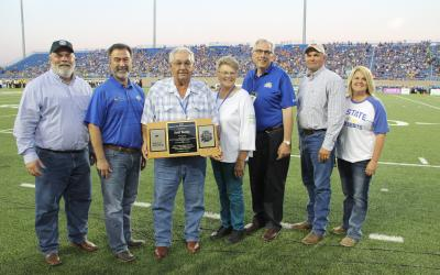 five men and two women standing in front of a packed stadium on the South Dakota State university football field accepting a wooden plaque for the friend of the beef industry
