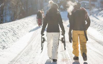 Two young women wearing layers of winter clothing walking down a snowy road