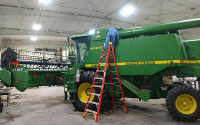 Producer on a ladder working on a green combine