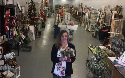 a woman standing in the isle of her store holding flowers
