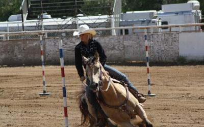 young cowgirl running a horse through the pole bending pattern
